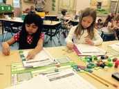 Lillie and Isabella using manipulatives to solve problems.