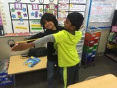 Ritvik and Rahul finding each other's arm span using a tape measurer.
