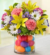 Colorful arrangment with egg filled vase and yellow lillies