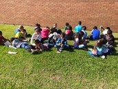 3rd grade reading their books on the lawn