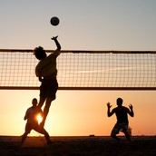 Some People Playing Volleyball On The Beach