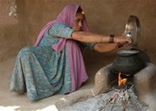 A person burning coal to boil water for cooking